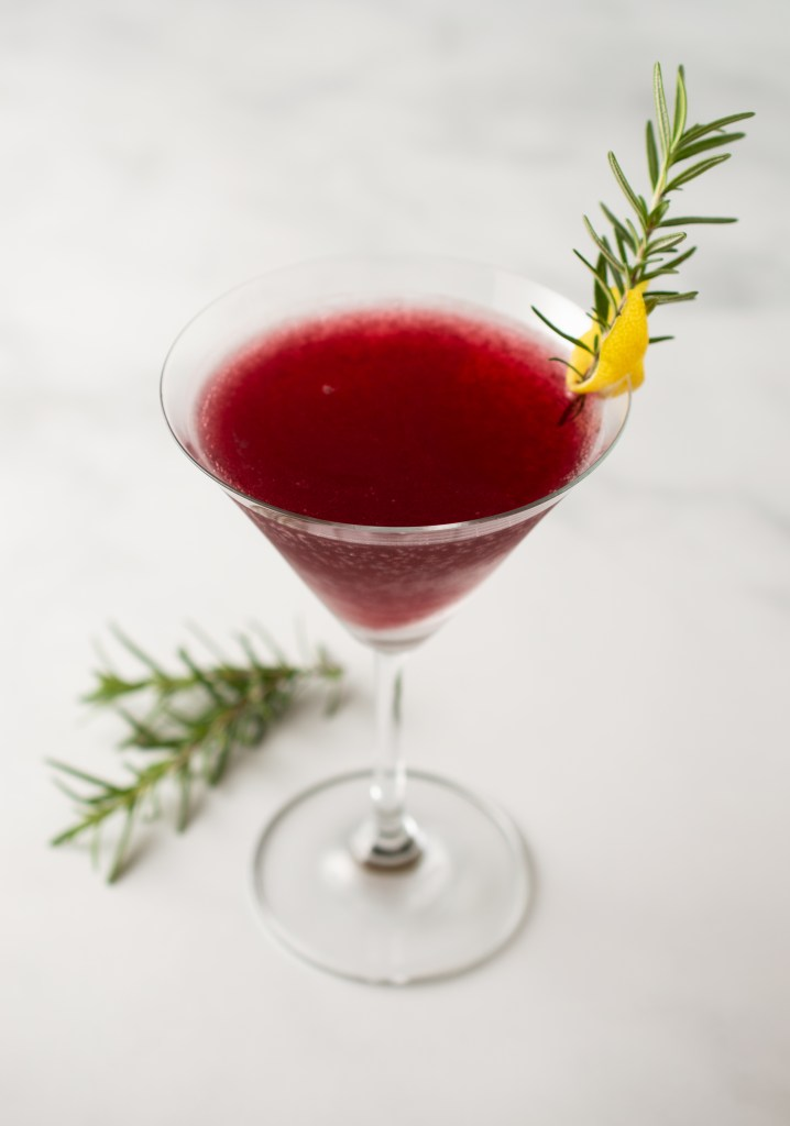 Pomegranate Rosemary Spritzer Mocktail in a martini glass garnished with a lemon twist and a sprig of rosemary