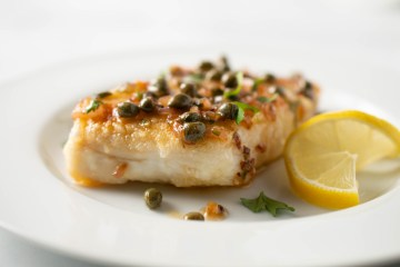Closeup of Halibut with Lemon Caper Sauce (AIP/Paleo) garnished with a twisted lemon wheel