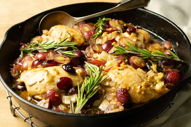Roasted Grape Chicken Thighs in a cast iron skillet atop an old-fashioned round cooling rack