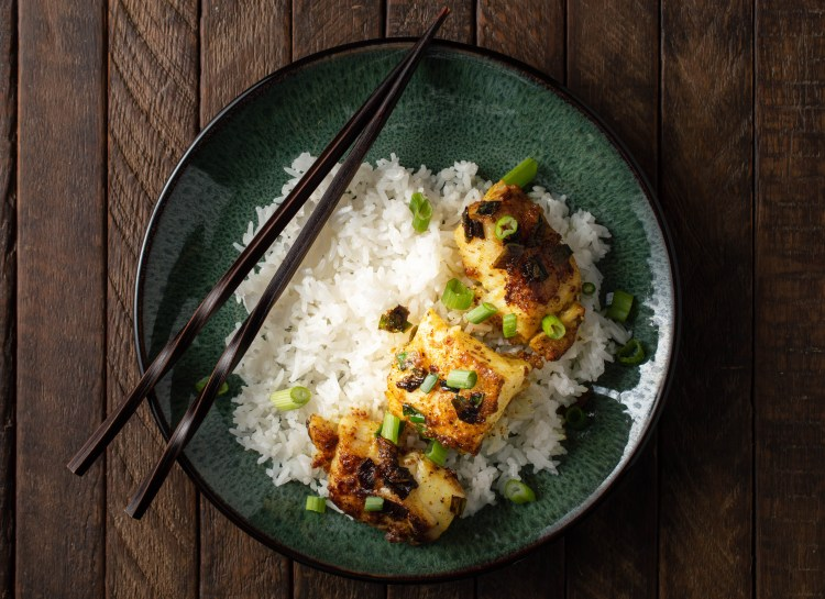 Overhead view of Gingered Cod (AIP/Paleo) over white rice on a green plate sitting on a dark wood surface.  The dish is garnished with sliced green onions and set off with chopsticks.