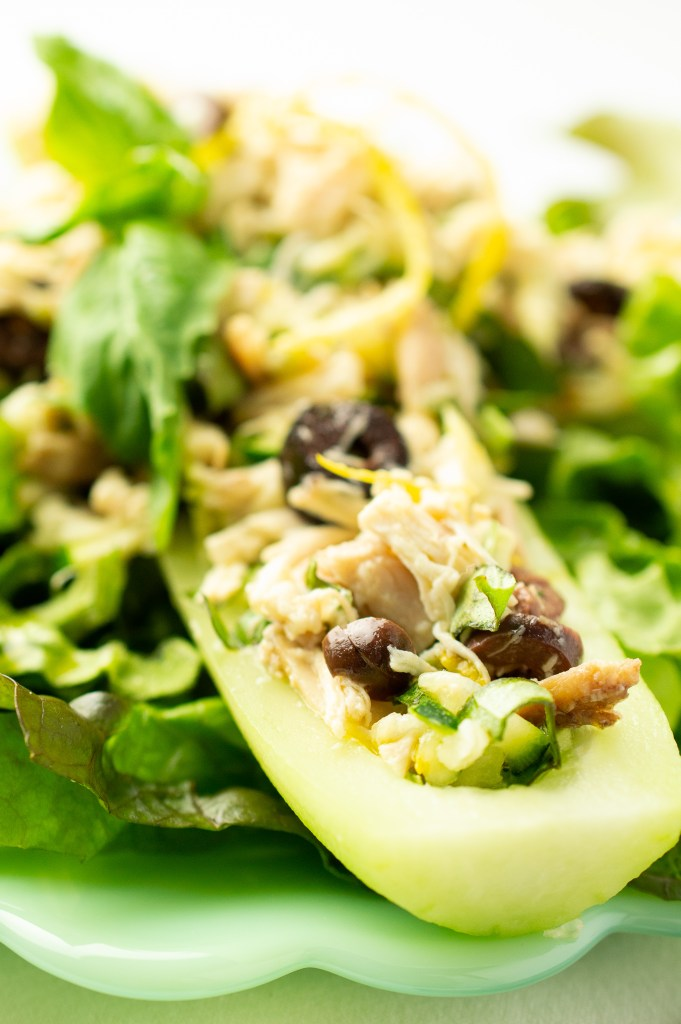 Close up of Mediterranean Chicken Salad (AIP/Paleo) in a cucumber boat. There are bits of lemon zest, Kalamata olives, and basil on top.