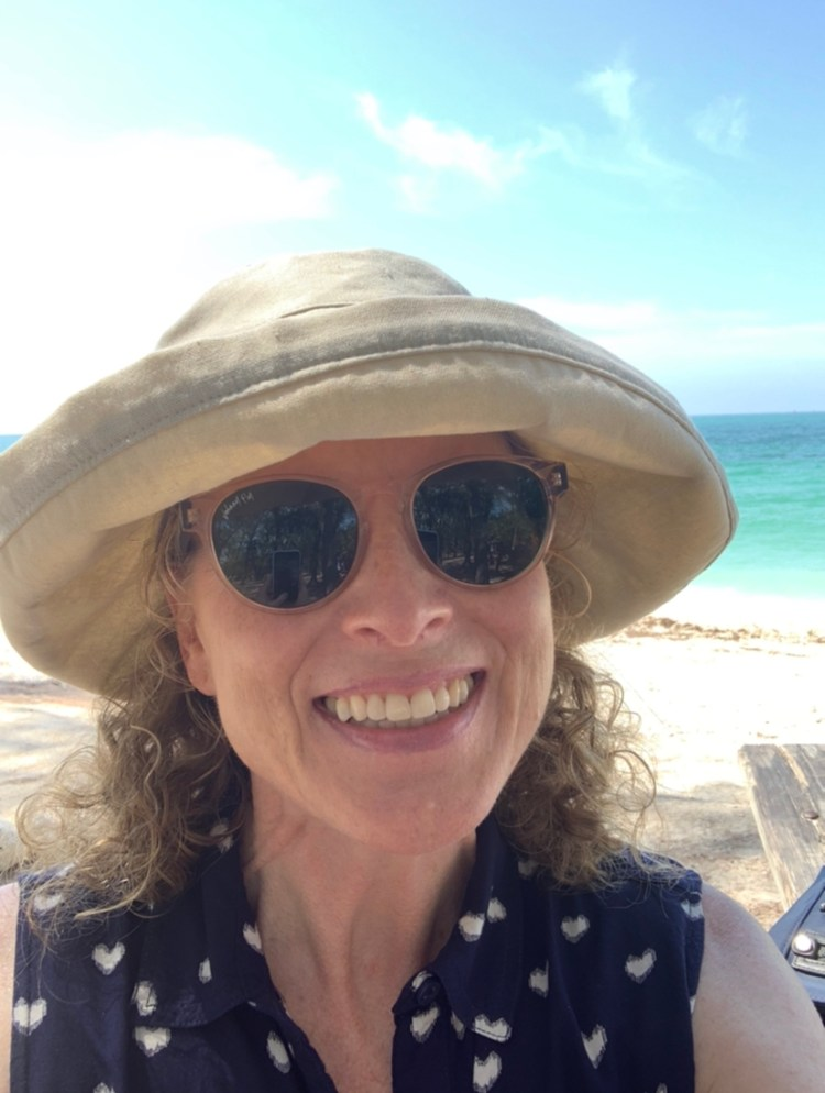 Wendi, a woman with curly blonde hair, smiles from under her sunglasses and sun hat.  She is on a beach, and she is so happy to be there.  She wishes she could be there now, but she digresses.