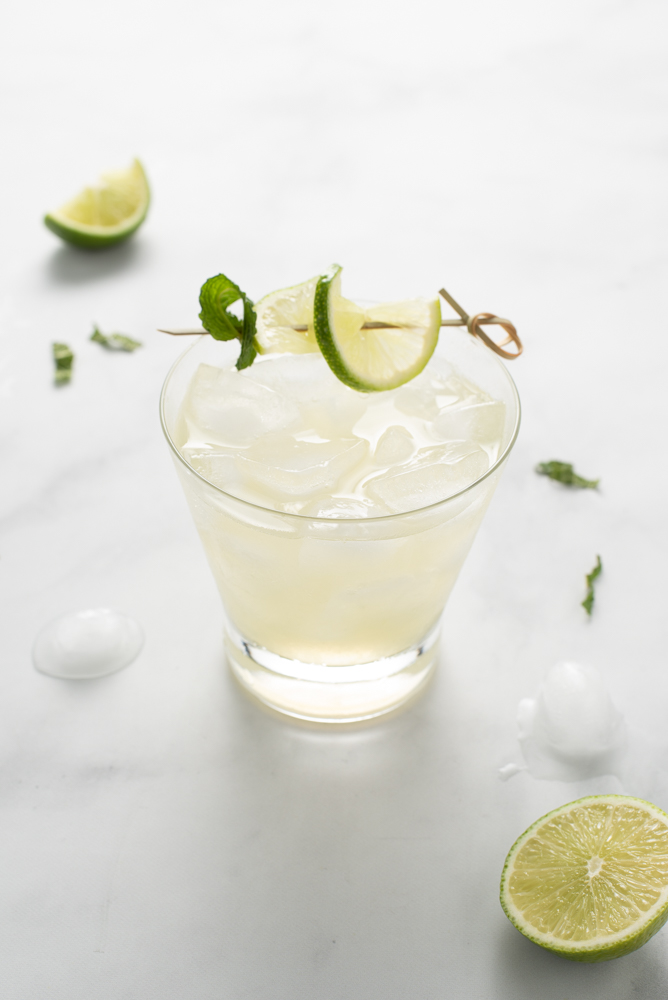 No-jito (AIP/Paleo) in a short cocktail glass with ice, garnished with lime and mint on a bamboo skewer. There is melting ice and lime pieces nearby.