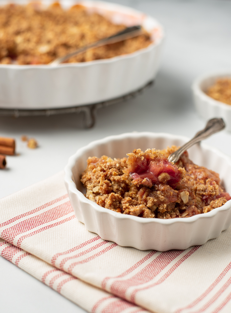 Closeup of Rhubarb Crisp (Paleo/AIP) in a small fluted serving dish on a striped dish towel.  The serving dish is in the background.