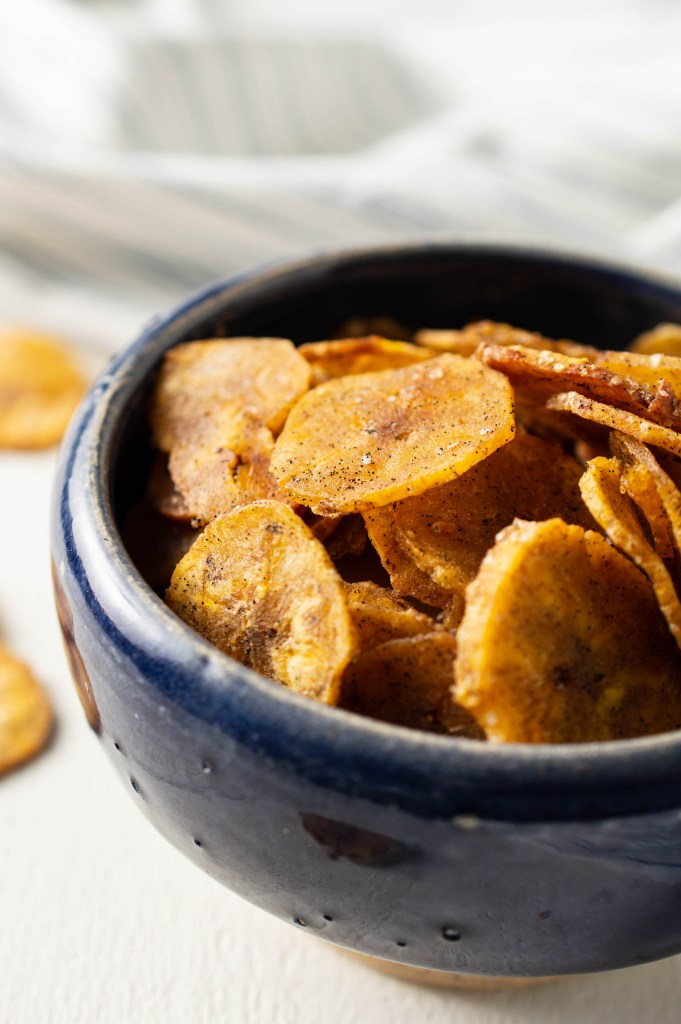 Closeup of Sweet & Salty Plantain Chips in a blue bowl. Flecks of vanilla and grains of vanilla salt cling to them.