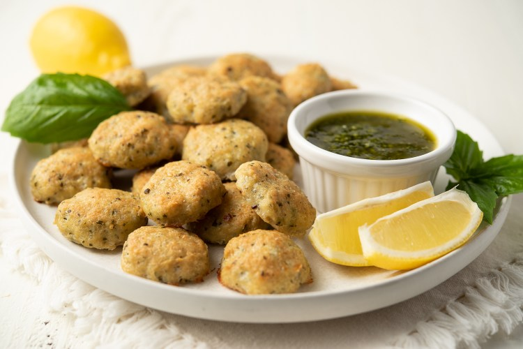 Lemon Pesto Chicken Poppers on a plate with a side of pesto and lemon wedges