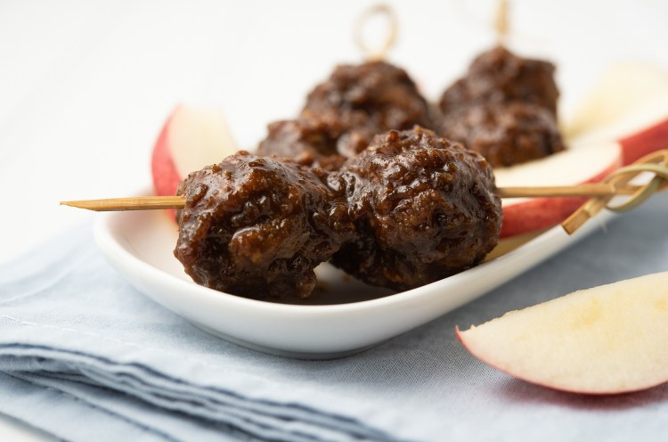 Apple Pork BBQ Meatballs on a bamboo skewer. There are three skewers on a small plate with apple slices nearby.