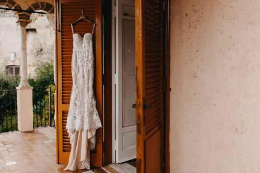 white wedding dress hanging on the door