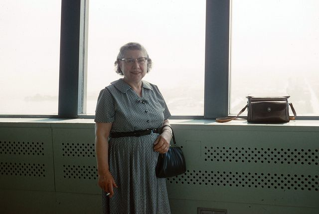 A happy visitor to the observation deck in 1962, cigarette in hand.  Photographer's handbag on ledge.