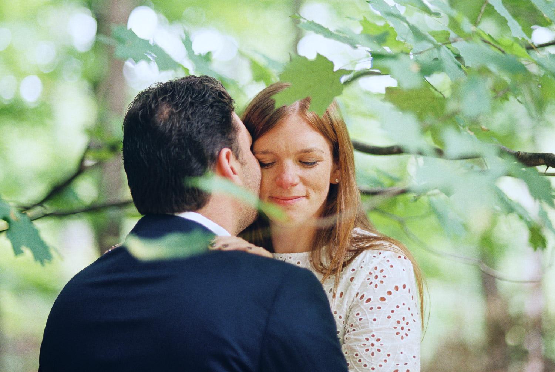 groom kissing bride's cheek in woods