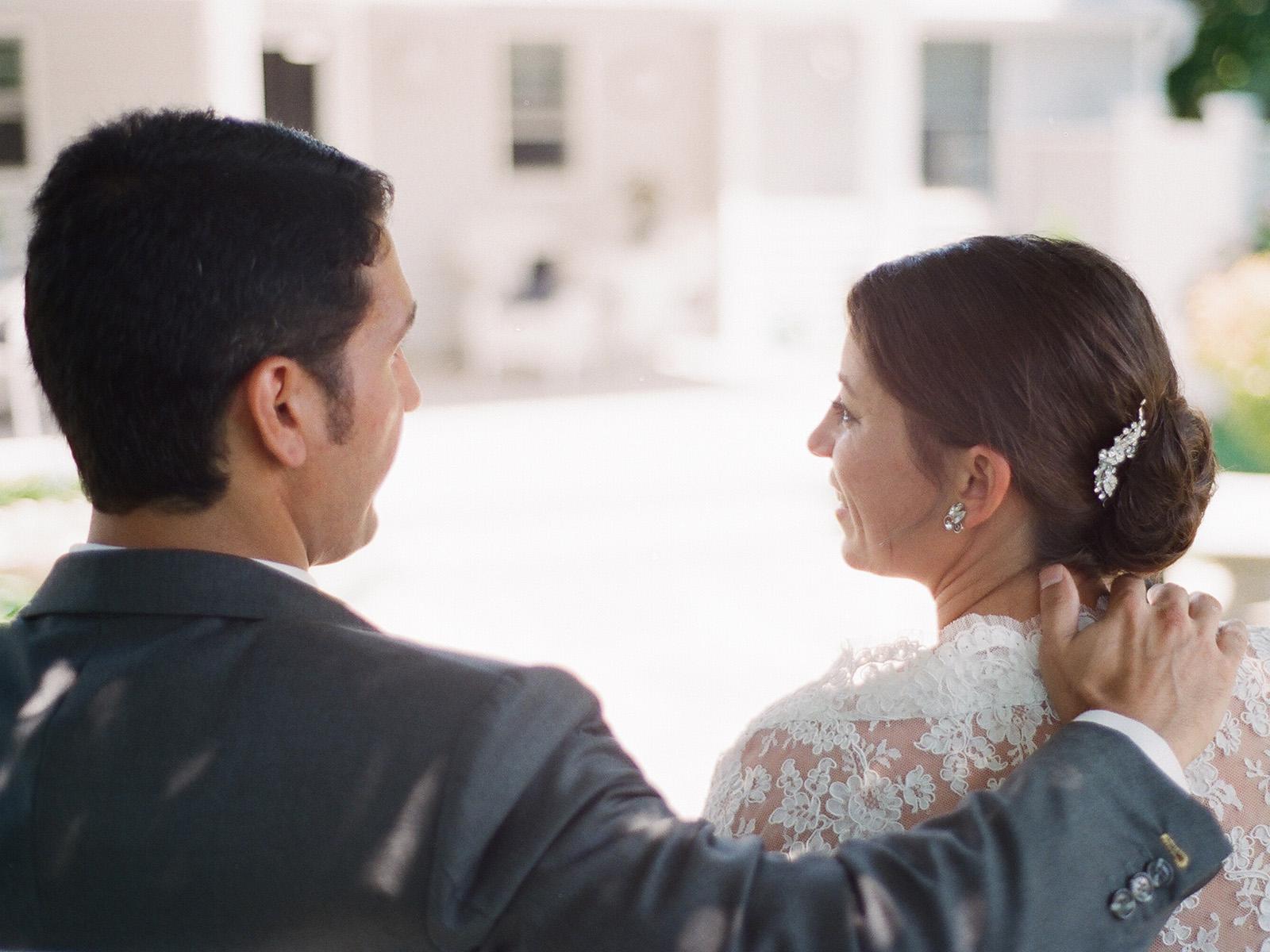 groom has hand on bride's shoulder