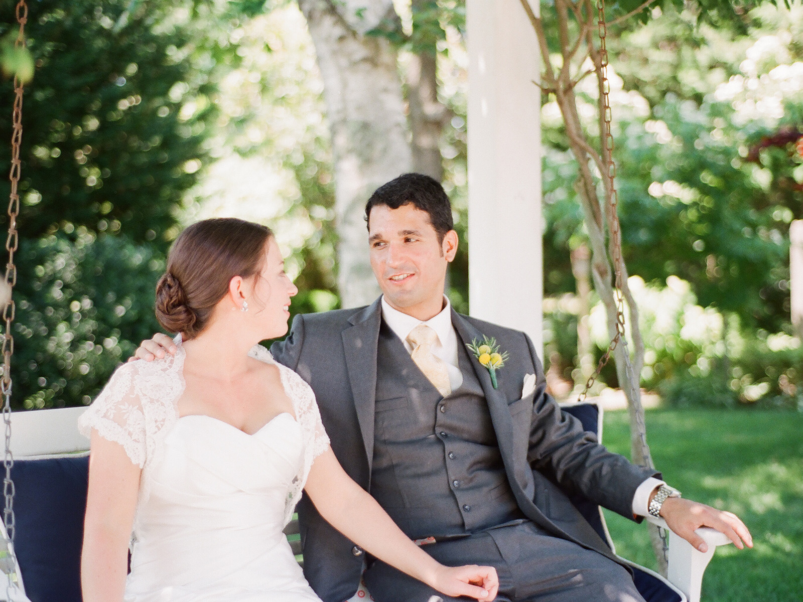 bride and groom sitting on bench swing