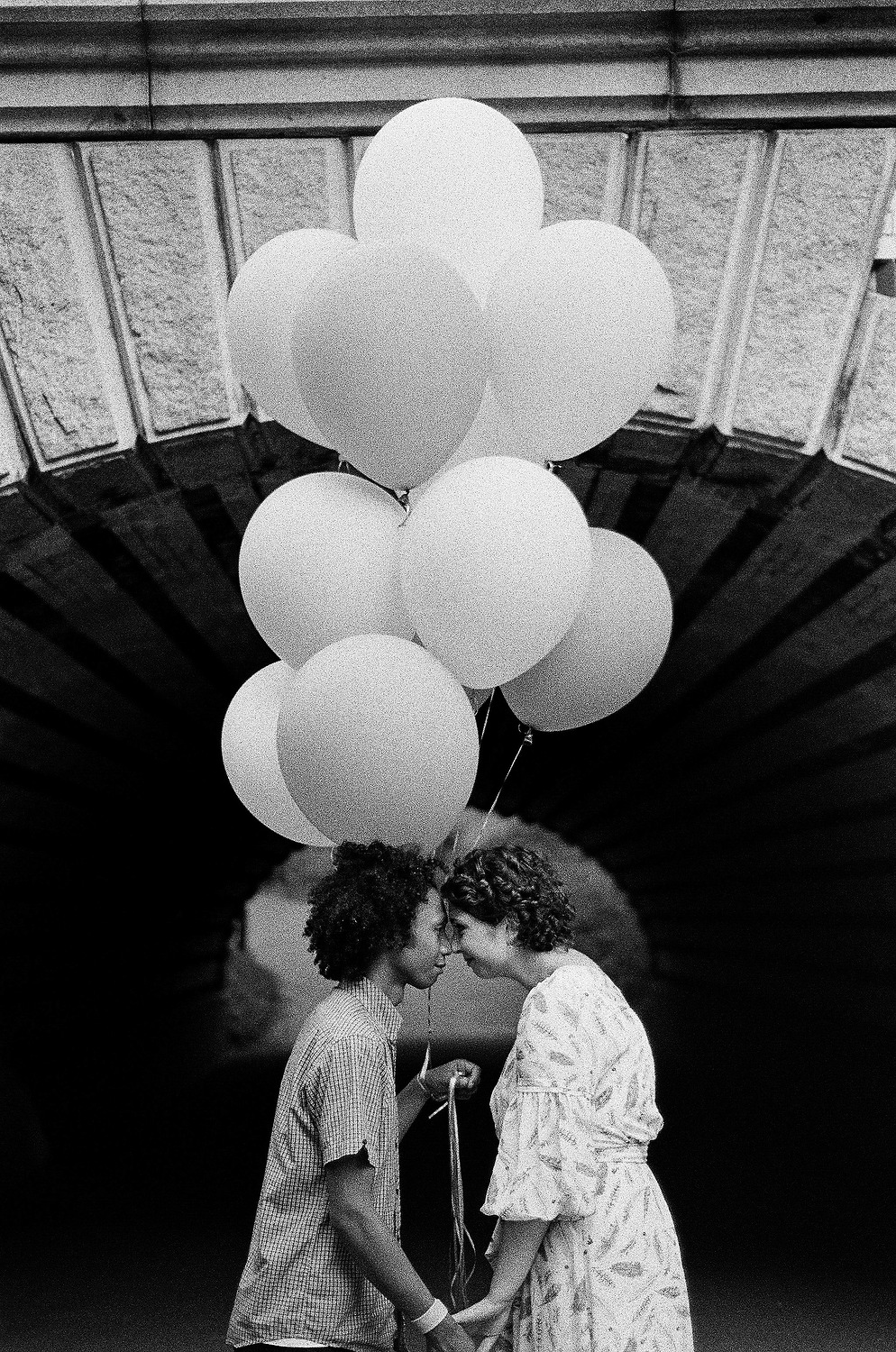 black and white photo of couple face to face and holding balloons