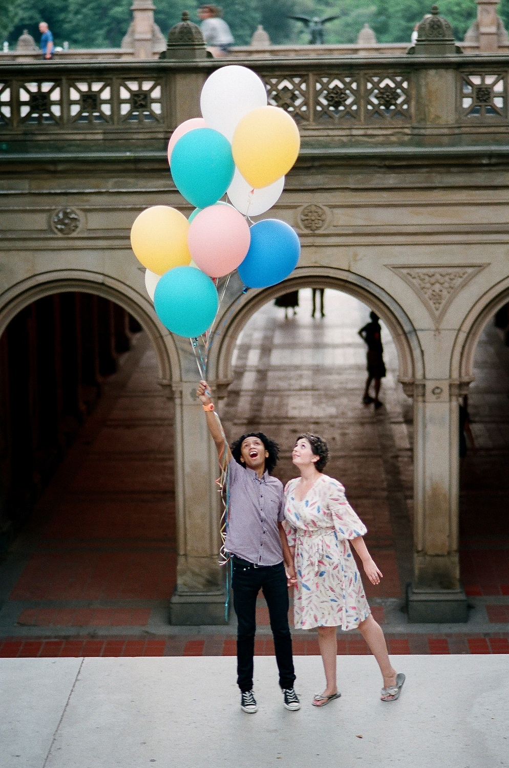couple being carried away by balloons