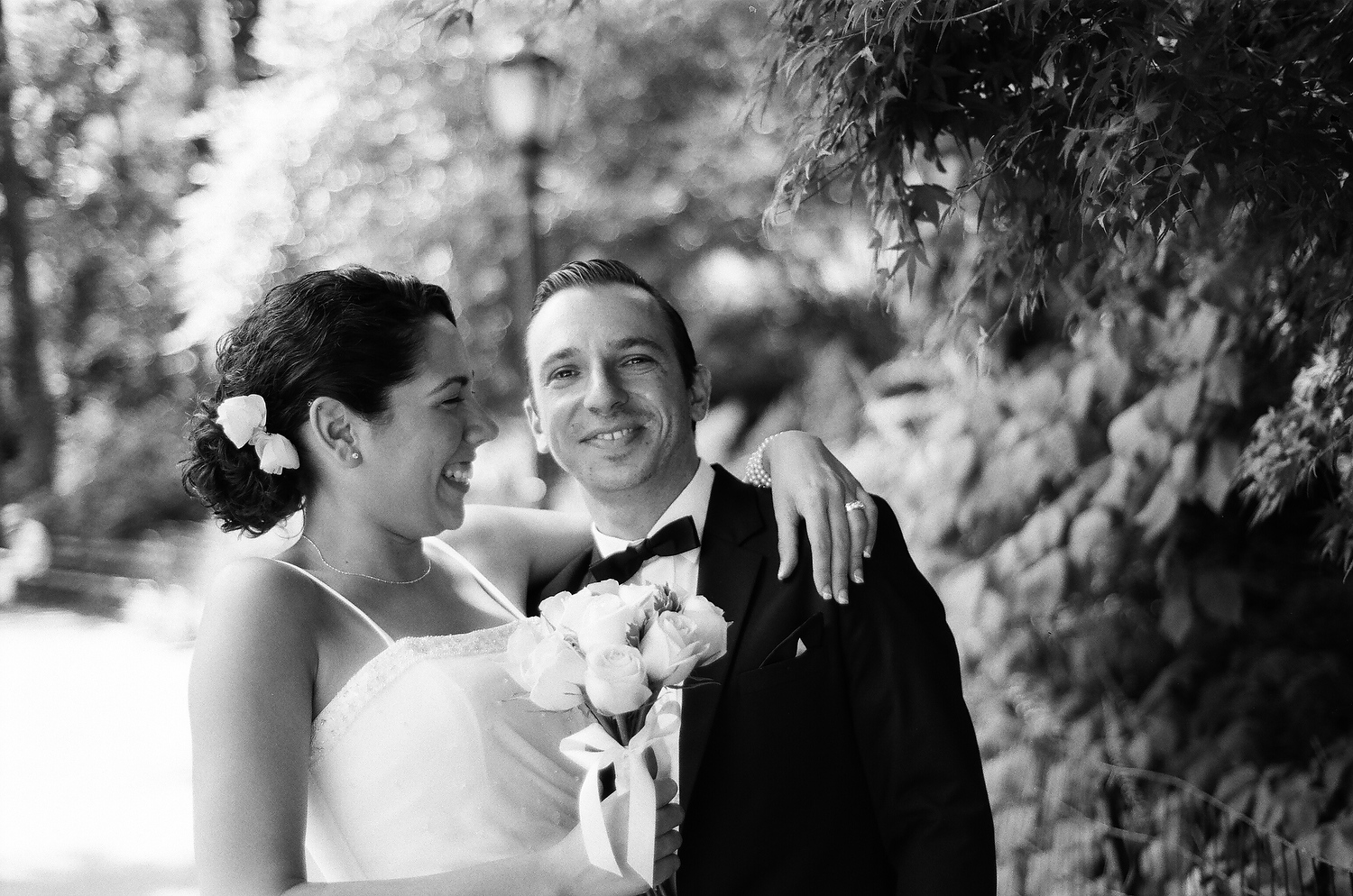 black and white photo of bride looking at groom in park