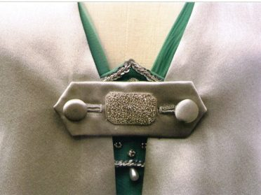 tab on the cloak has hand sewn buttonholes and silver embroidery