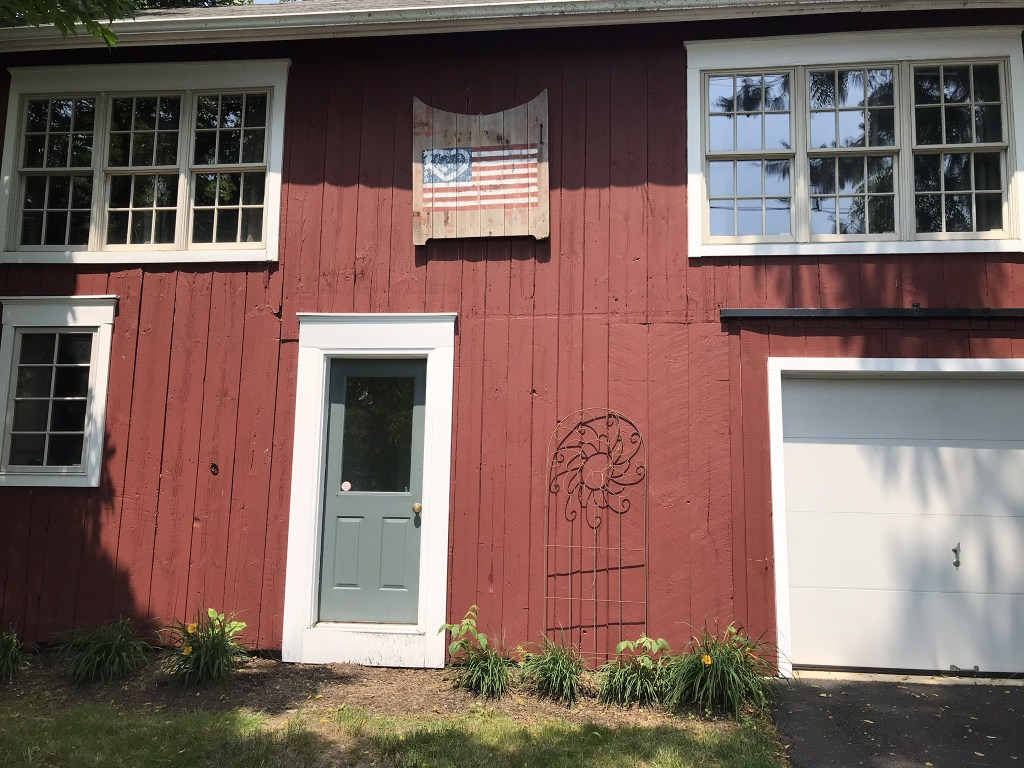 A big red barn with the gate American Flag painted on it