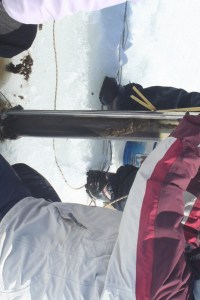 The core sample emerges from the hole in the ice.