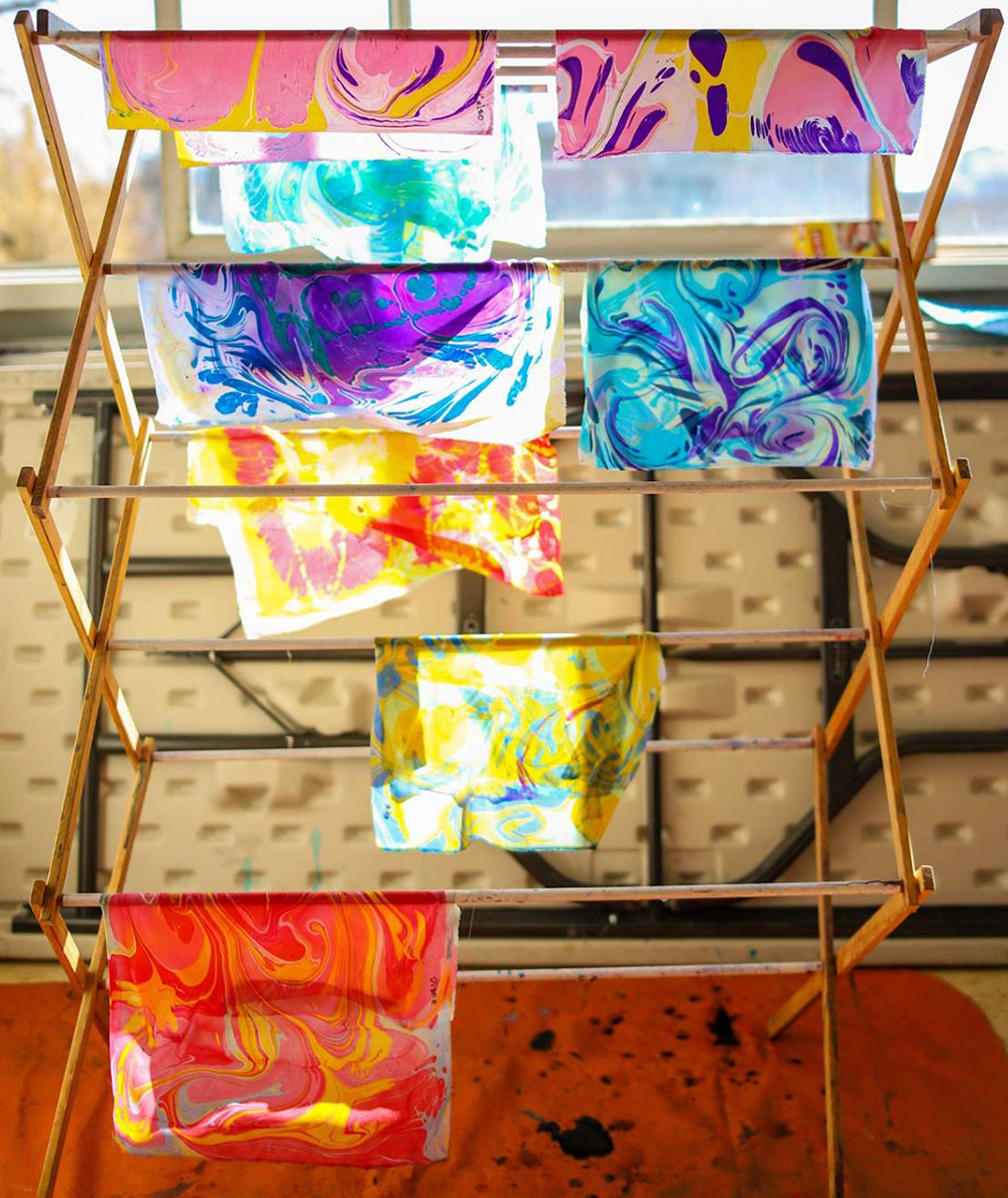 photo of samples of marbled fabric hanging on a drying rack - each piece is a mixture of marbled colours - by Dora Prieto