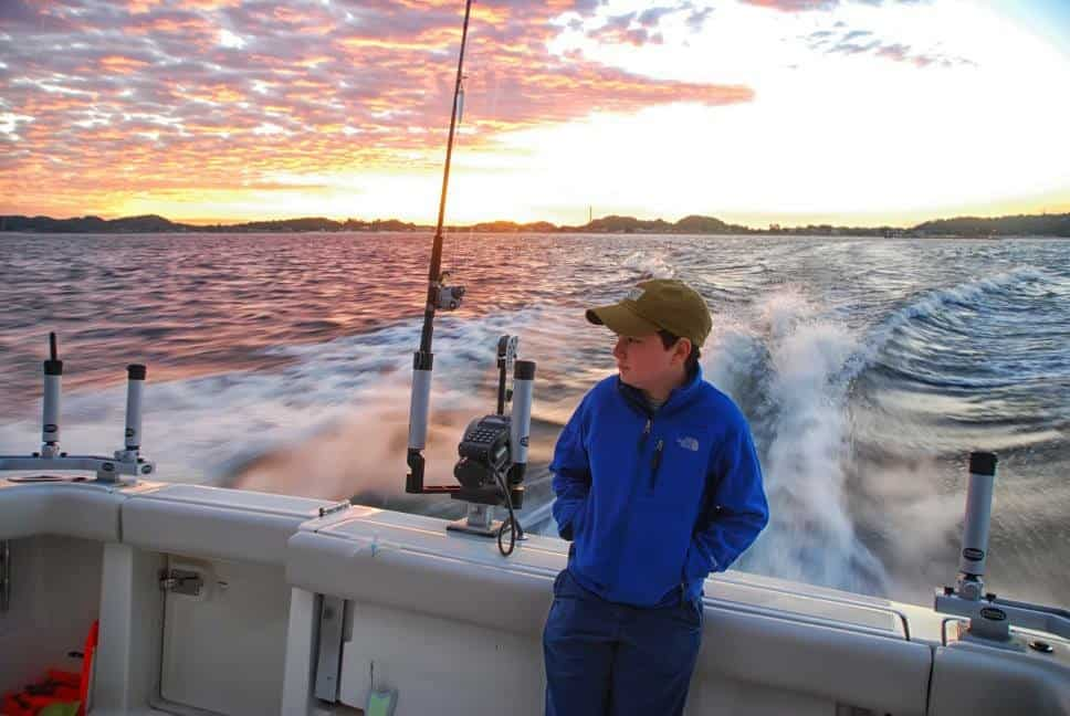 Young man on the back of a charter boat heading out to Lake Michgan