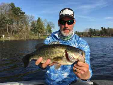 Man holding a largemouth bass caugh on the Grand River