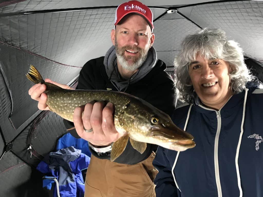 Man holding a norther pike next to a lady ice fishing
