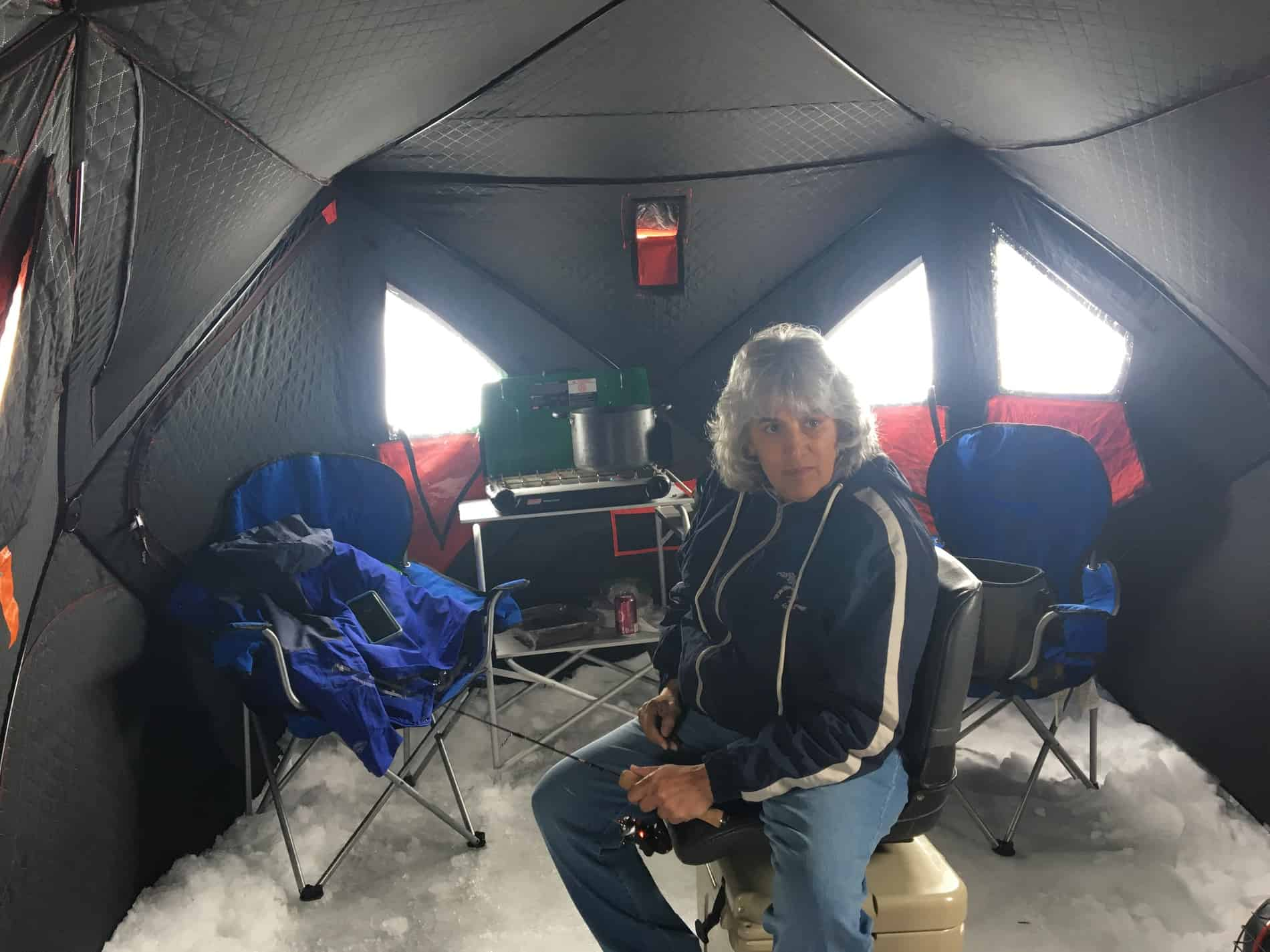 Woman in an ice shanty on Hamlin Lake ice fishing