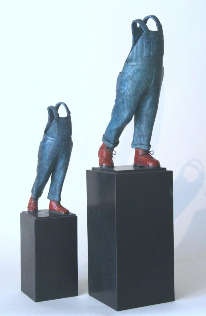 Photo de deux versions en bronze a patine polychrome rouge noire nuancée et bleue nuancée de A Coluche, la scupture de Guillaume Werle en hommage au célèbre comique.