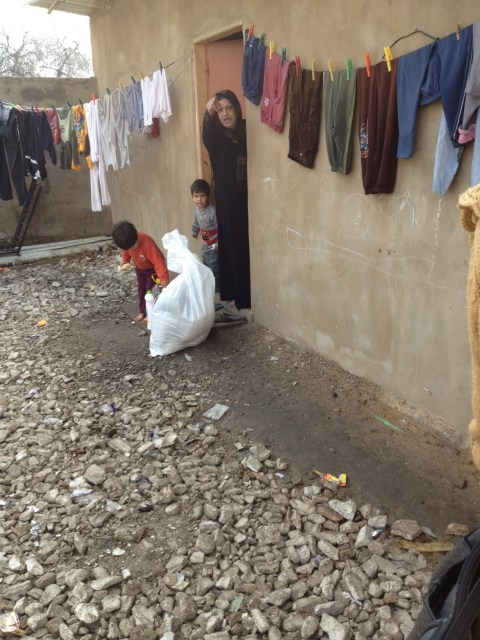 A refugee being provided food and cleaning supplies by Mission ONE partner, AFA Middle East Team