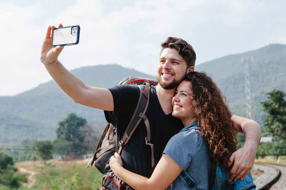 happy couple of travelers taking selfie on smartphone in nature in daytime