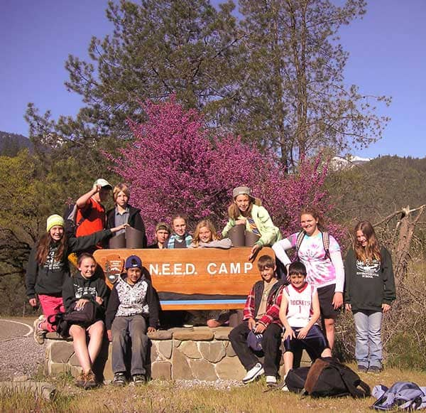 Kids sitting in front of NEED Camp sign