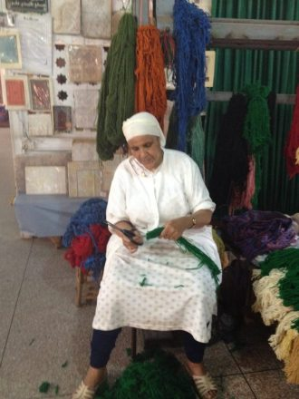 A Moroccan artisan is sorting thread colors before weaving a carpet. Courtesy photo