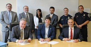 Dan Drew signing Memorandum of Understanding on sexual assault with Middletown Police Chief and Wesleyan officials.