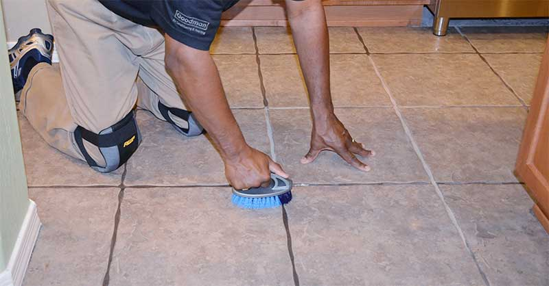 scrubbing the dirty grout lines with brush