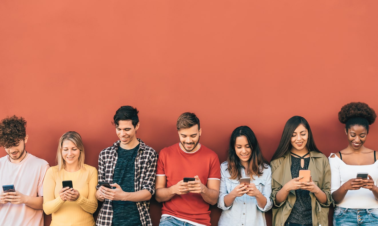 A concept of brand positioning; a group of Gen Z consumers against a wall using their mobile phones for online shopping