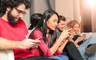 Group of diverse Gen Z people sitting on a couch while using their mobile phones.