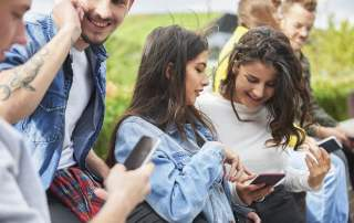 Happy group of diverse Gen Z people using their mobile phones to check on StockTok application.