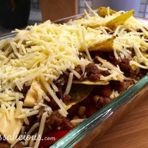 Afwerking Nacho-ovenschotel, geraspte kaas en vegetarisch gehakt