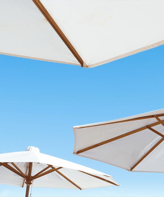 image of white patio umbrellas on a blue sky