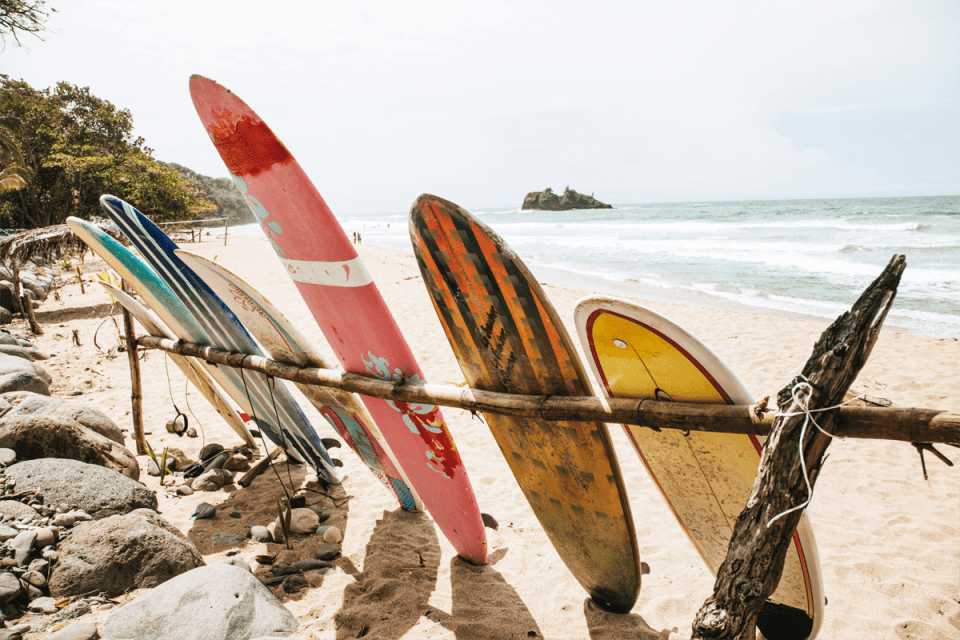 colorful surf boards leaning against a handmade wood rack on a beach with the ocean in the background