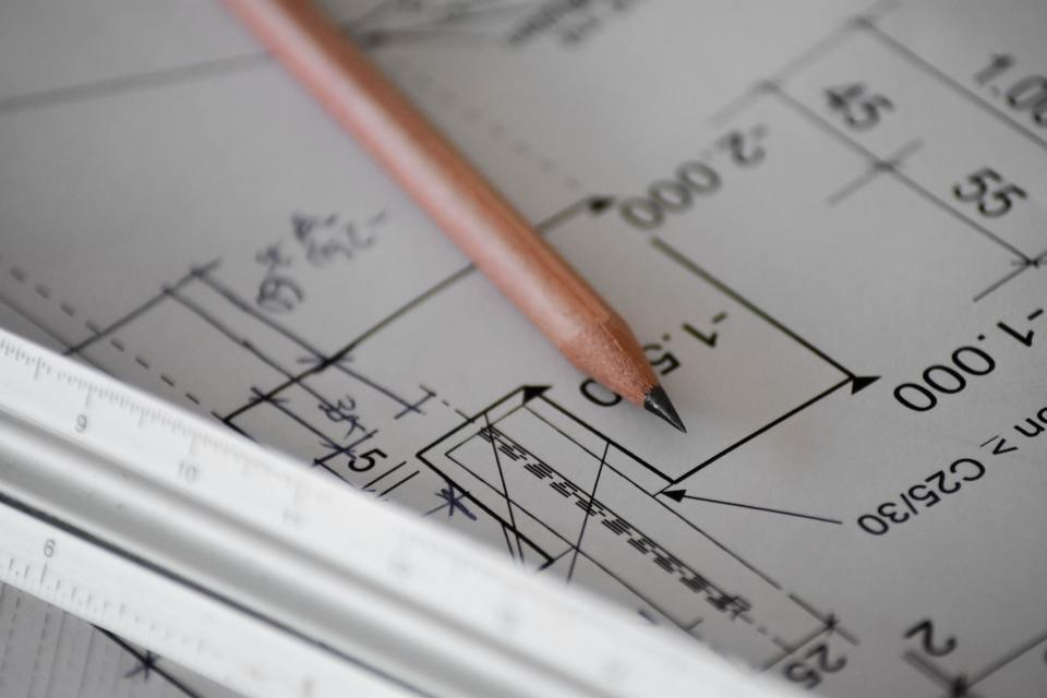 photo of a sharpened pencil and a scale ruler sitting on top of an architectural drawing