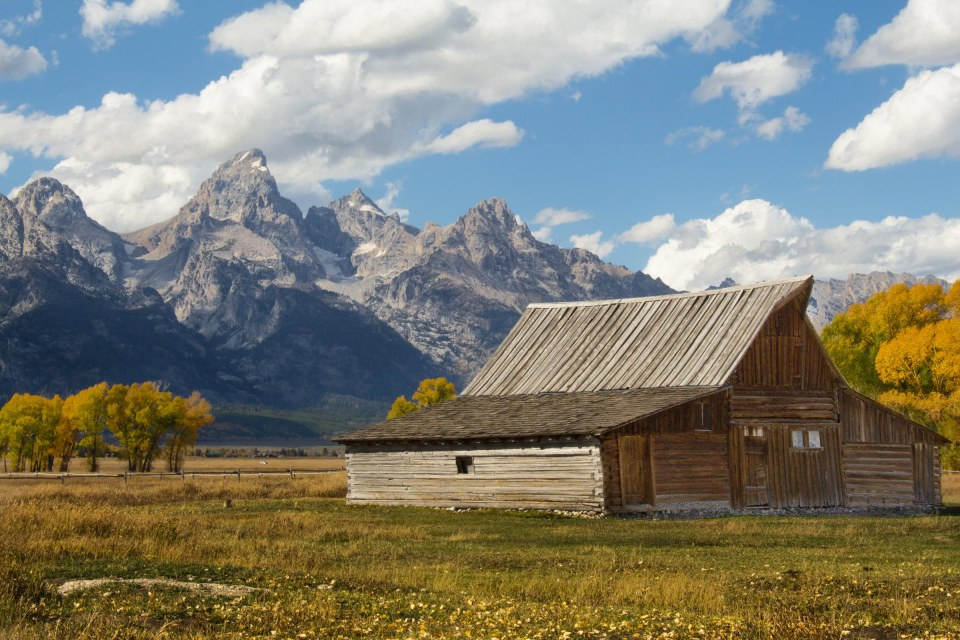 photo of a rustic farmhouse with weathered roof and siding surrounded by prairie grass at the foot of the teton mountain range