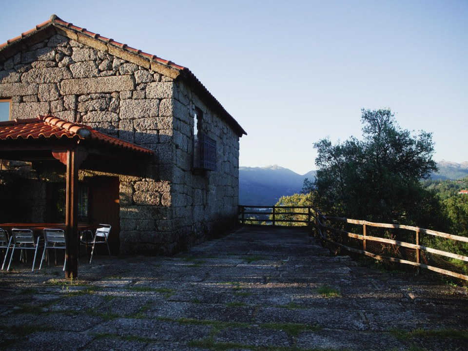 photo of a stone farmhouse with a tile roof, next to a stone paver road
