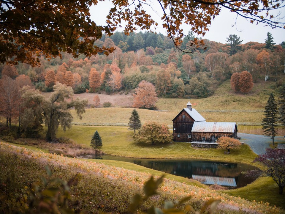 photo of a barn and farmhouse nestled in a valley with fall trees surrounding it