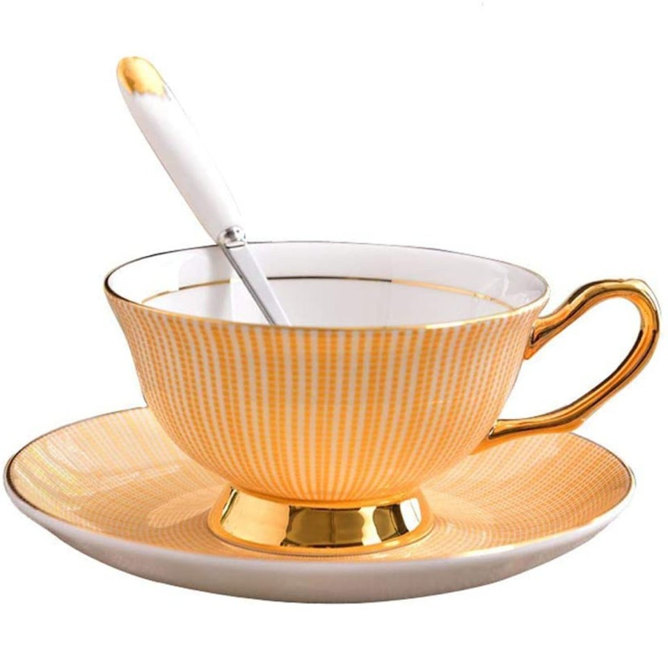 a yellow and gold tea cup and saucer set with matching china spoon