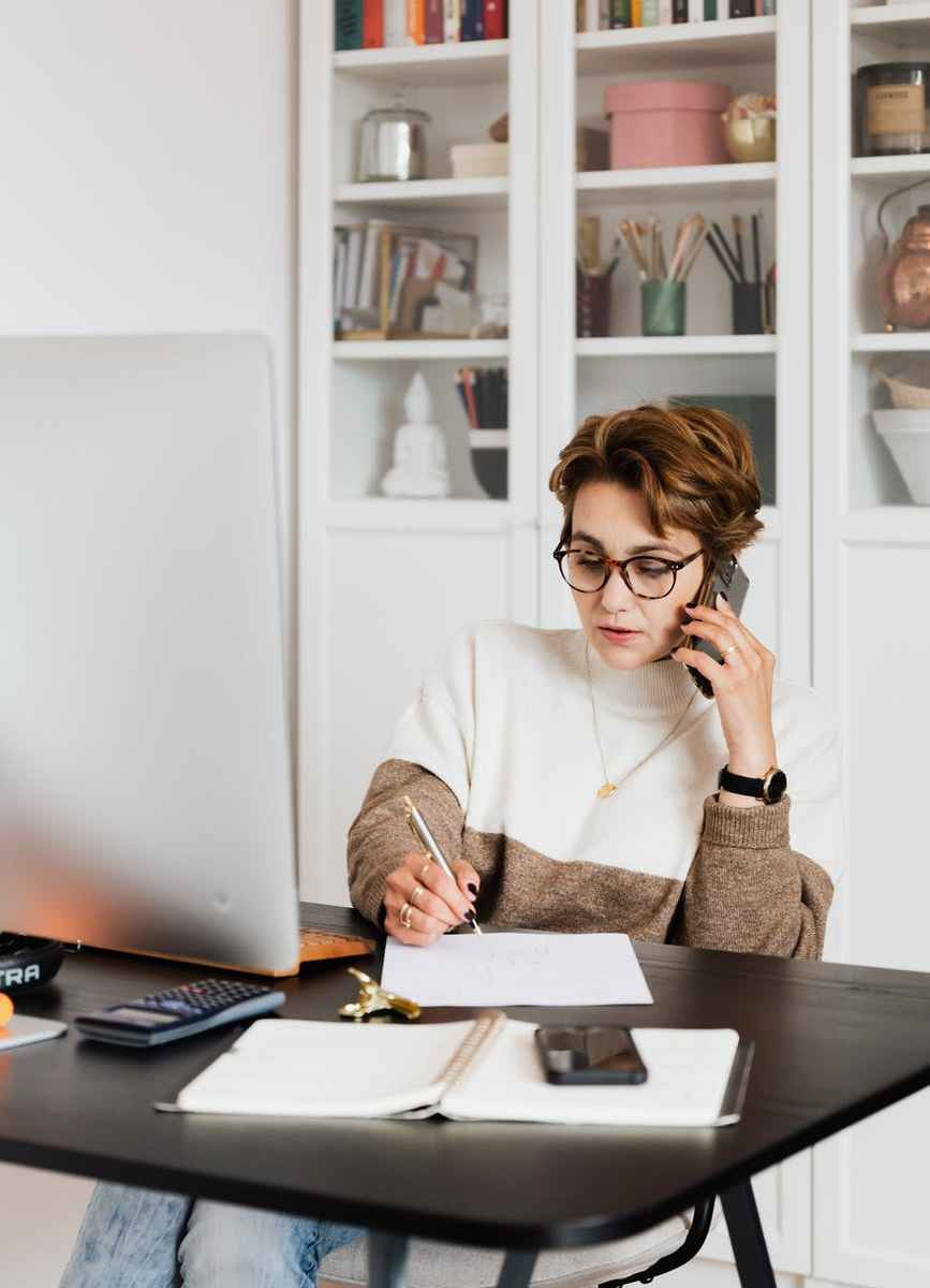 modern businesswoman in casual outfit talking on mobile in office