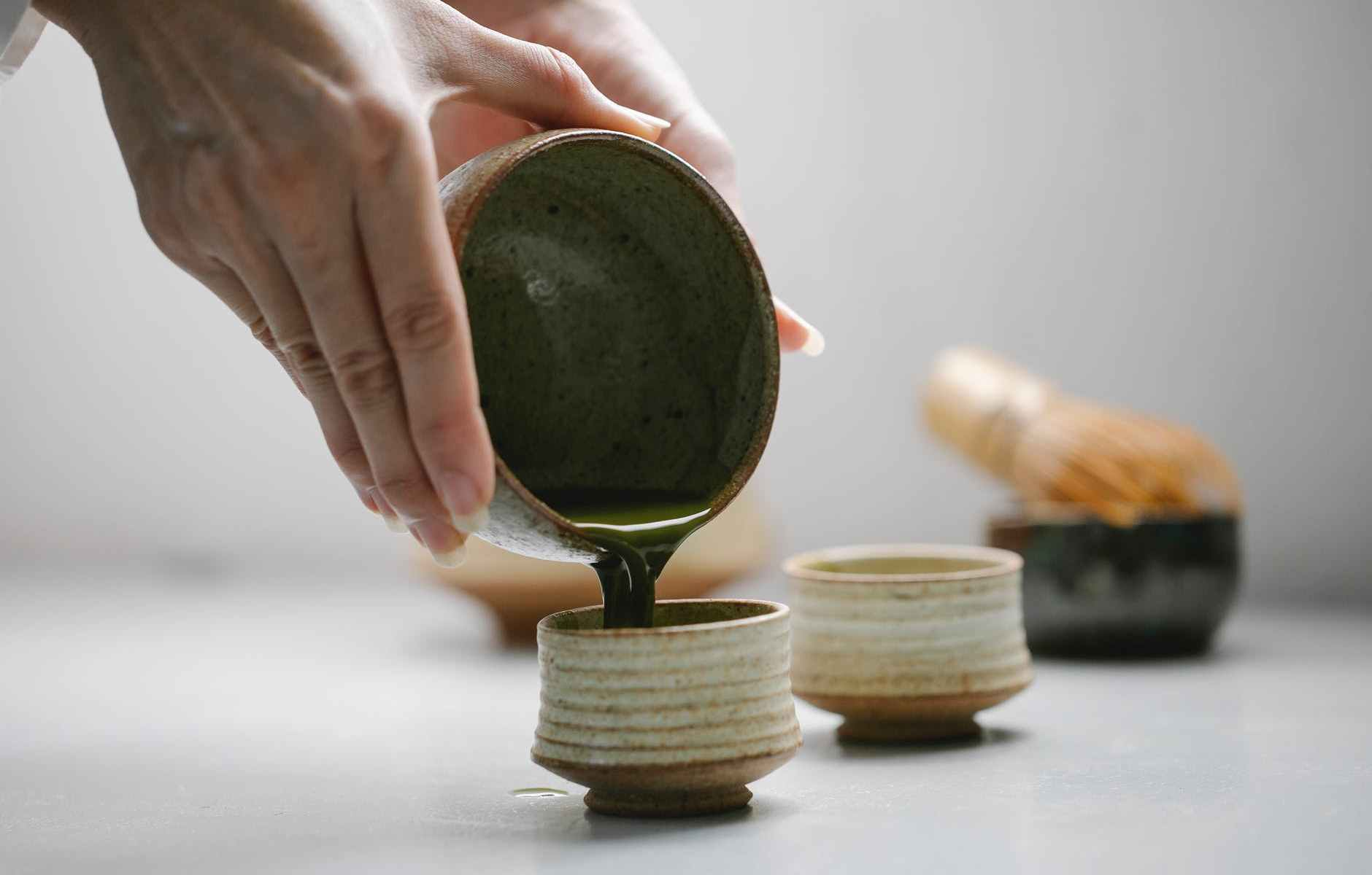 woman pouring tea into cups for tea ceremony