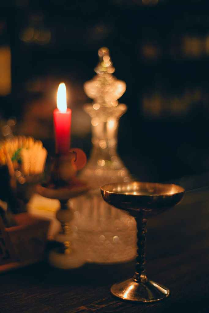 burning candle near metal bowl and carafe in church