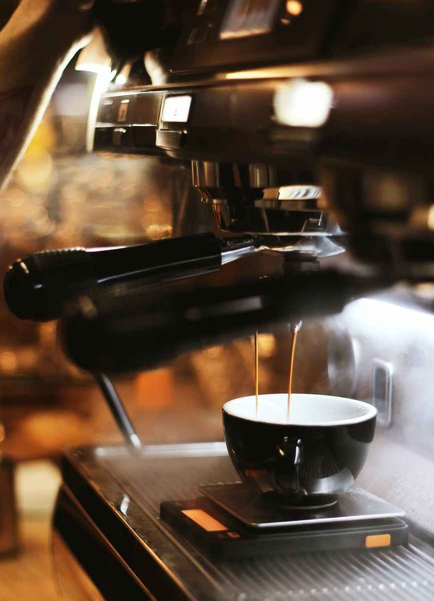 black espresso maker with cup