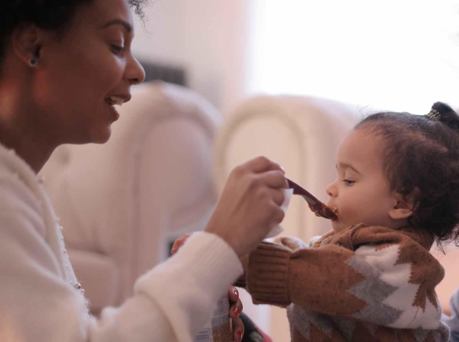 photo of woman feeding her child